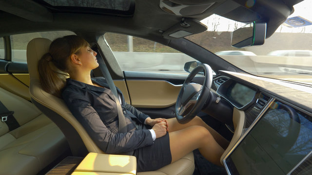 CLOSE UP: Young woman napping in an autonomous car driving her along the freeway