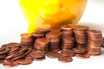 closeup of yellow piggy bank with cents of euro coins piles  on white background
