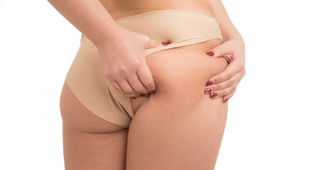 young woman pinching fat on her buttocks on white background