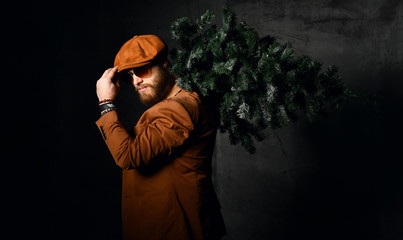 Brutal bearded man in brown leather jacket and cap hat aviator sunglasses hold Christmas tree