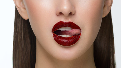 Close-up of sexy female lips with tongue. Clean skin and a clear lip contour are outlined with a fashionable red lipstick. White teeth and the beauty of a smile for stamotologii, spa or cosmetology