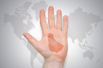 hand with map of barbados on the gray world map background.