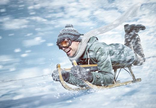 Mann in voller Fahrt beim Rodeln im Schnee