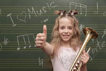 Ein Mädchen mit Trompete hält Daumen hoch