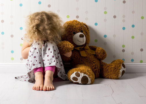 Little curly haired girl is crying in her room. Little girl is missing a sibling. Little girl wants little brother.