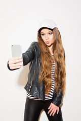 Teenage girl with long natural blonde hair in black and white outfit, taking a selfie on smart phone, making a kissy face, on white background. Studio lighting, no retouch.