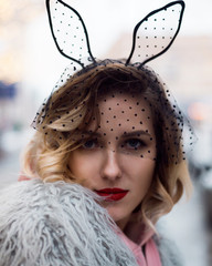 Cute blondie girl in fashion artificial fur coat and black veil with rabbit ears and red lips outside winter.