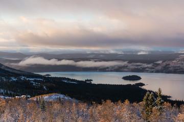 Wolkenverhangener See mit Schneelandschaft