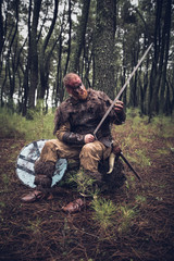 viking with red beard with armor shield and sword in the battle field