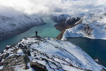 Blick vom verschneiten Besseggen-Grat mit Silhouette eines Wanderers