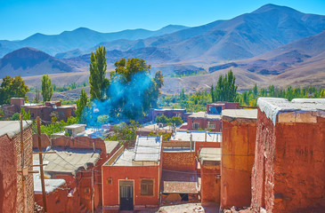 Enjoy the landscape of Karkas mountains from the terrace adobe village of Abyaneh with preserved reddish houses, Iran.