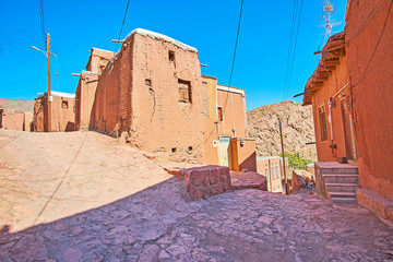 The medieval stone street branches into different directions with a view on the old adobe edifices in the middle, Abyaneh, Iran.