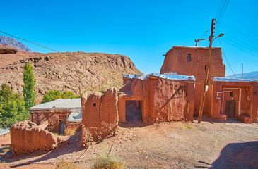 The line of old reddish mud houses of Abyaneh village with rocky mountain slope on the background, Iran.