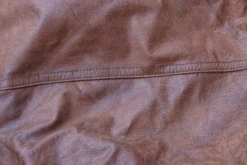 brown texture of crumpled leather with a seam on clothes
