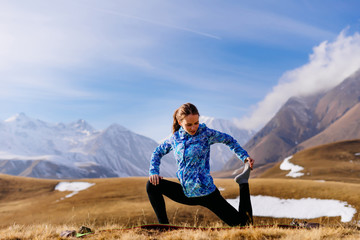 A young athletic girl in the background of the Caucasian high mountains is engaged in yoga, leads a healthy lifestyle