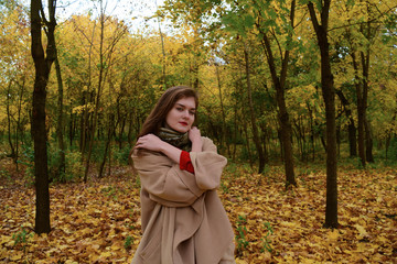 Girl in coat on autumn Park background.
