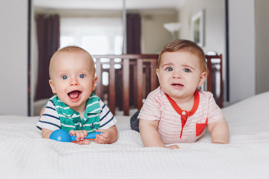 Group portrait of two white Caucasian cute adorable funny baby boys lying together on bed sharing toy. Friendship childhood concept. Best friends forever. Early years development