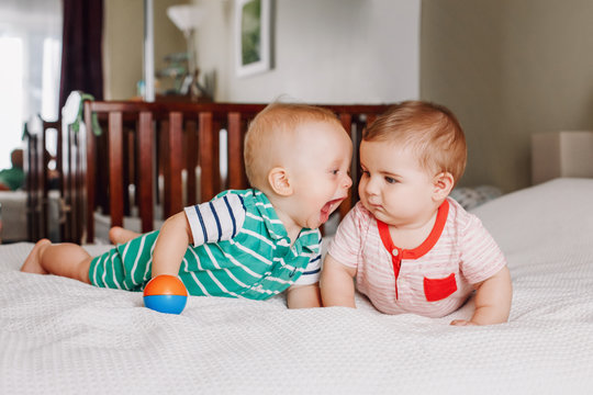 Group portrait of two white Caucasian cute adorable funny baby boys lying together on bed communicating and playing. Friendship childhood concept. Best friends forever. Children fighting