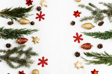 Christmas composition. Frame from christmas red and gold decorations, fir tree branches, pine cones on white background. Flat lay, top view, copy space