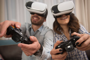 couple playing video games wearing virtual reality glasses.