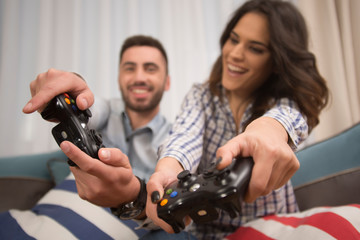 happy smiling couple playing video games at home.