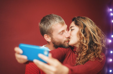Happy couple making a selfie with mobile smartphone app - Young lovers having fun taking selfie with phone camera - Relationship, love and technology trends concept