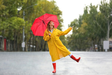 Happy young woman with red umbrella in city on rainy day