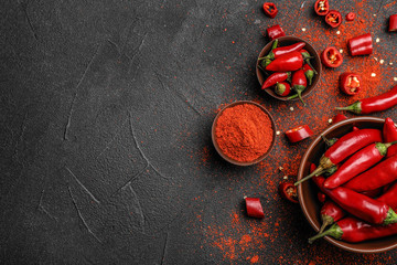 Canvas Prints Hot chili peppers Flat lay composition with powdered and raw chili peppers on dark background. Space for text