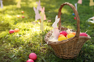 Basket with Easter eggs and decor on grass in park. Space for text