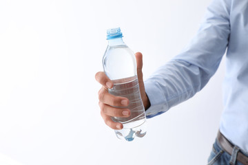 Man holding bottle of pure water on white background, closeup. Space for text