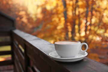 Hot cozy drink in cup on wooden railing at balcony. Space for text Fototapete