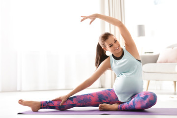 Young pregnant woman in fitness clothes practicing yoga at home. Space for text