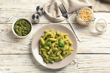 Flat lay composition with plate of delicious basil pesto pasta on wooden table