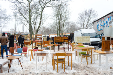 Atmosphere of people shopping second hand vintage furnitures, clothes and stuffs show on the ground covered with snow at Fleamarket at Mauerpark in winter season.
