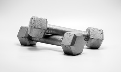 two well worn 5 pound silver dumbbells isolated on white