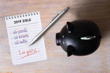 Sparschwein und Notizblock mit Zielen für 2019