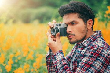 Young hipster man taking photo with retro camera.