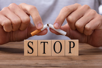 Man Breaking Cigarette Over Stop Blocks