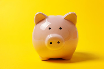 Pink piggy bank isolated on yellow colourful trendy modern fashion background. Saving investment budget wealth business retirement, financial, money, banking concept. Copy space