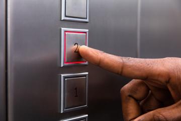Man Pressing On Second Floor Elevator Button