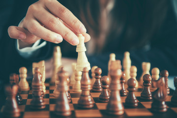 Businesswoman moving chess figure with team behind - strategy or leadership concept
