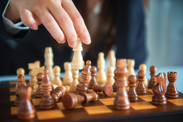 Businessman moving chess figure with team behind - strategy or leadership concept