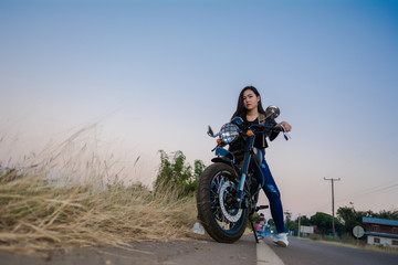 Young sexy woman on a motorcycle in nature on the sunset.Travel Concept.