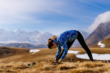 active sports girl engaged in yoga in nature, the Caucasus mountains, loves to travel