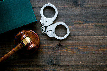 Crime concept. Metal handcuffs near judge gavel and law book on dark wooden background top view copy space