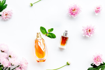 Floral perfume for women. Bottle of perfume near delicate pink flowers on white background top view pattern