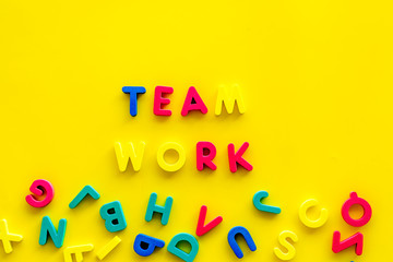 Teamwork training concept. Text teamwork lined with colored letters near toy letters on yellow background top view copy space