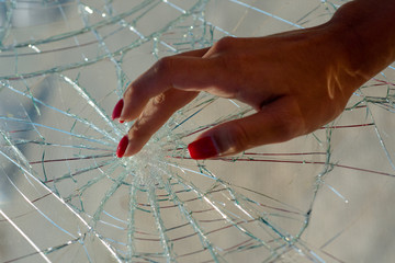Sensual touch. Nail care and nail protection. Red manicure. Broken glass.