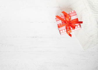 A festive gift decorated with a red silk ribbon and bow on a white wooden background. Winter New Year or Christmas concept. Place for design and text. Flat layout. View from above.