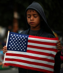 A migrant boy from Honduras holds a U.S flag in front of Mexican riot police at the El Chaparral port of entry border crossing between in